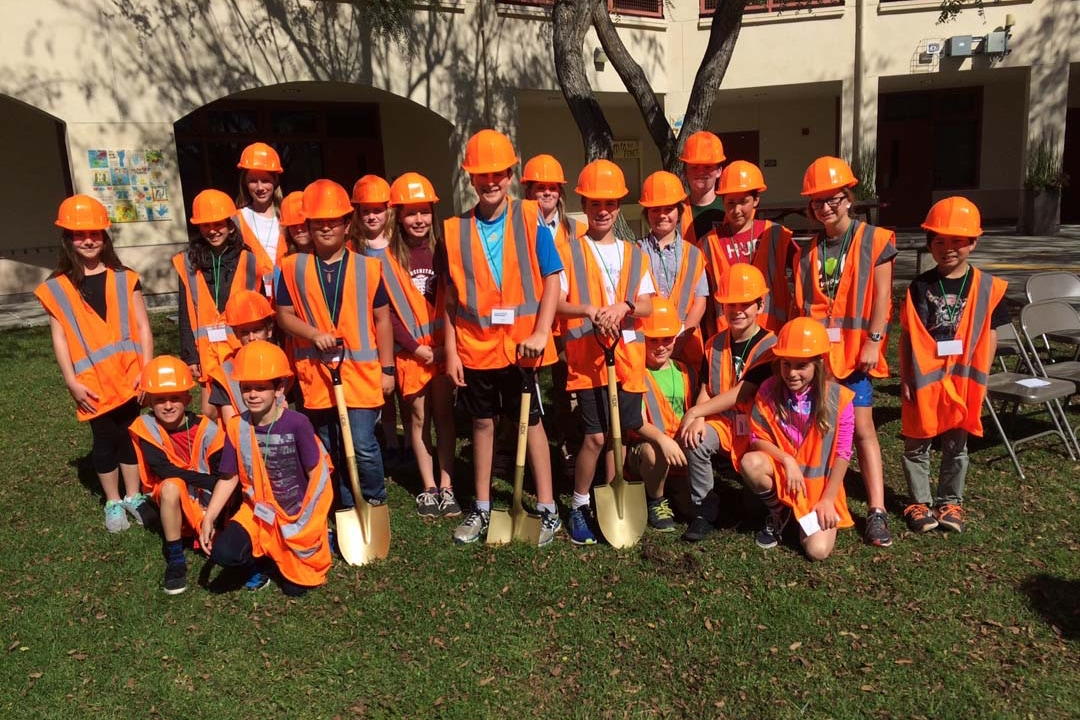Large group of students in bright orange vests and hardhats before their groundbreaking ceremony on their state funded water quality project