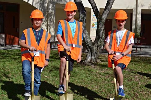 3 SWPPP interns posing in bright orange vests with shovels preparing for the start of the DROPS funded project at their school