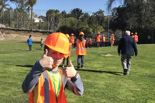 SWPPP Intern gives the camera double thumbs up as they tour the site of their future bioswale with contractors bidding on the project