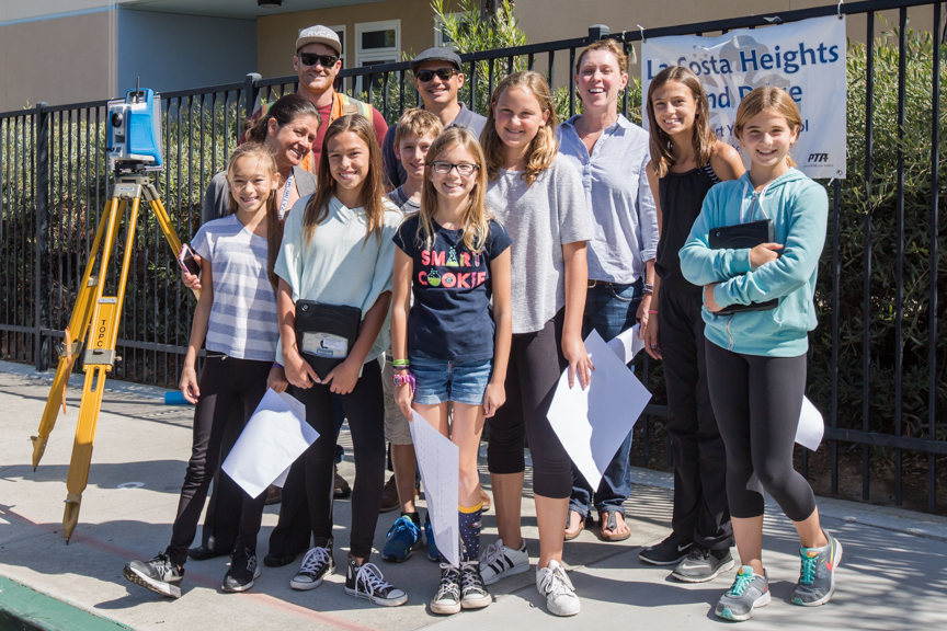 Group of elementary school interns from La Costa Heights with a survey team and civil engineer preparing for the on campus water quality project
